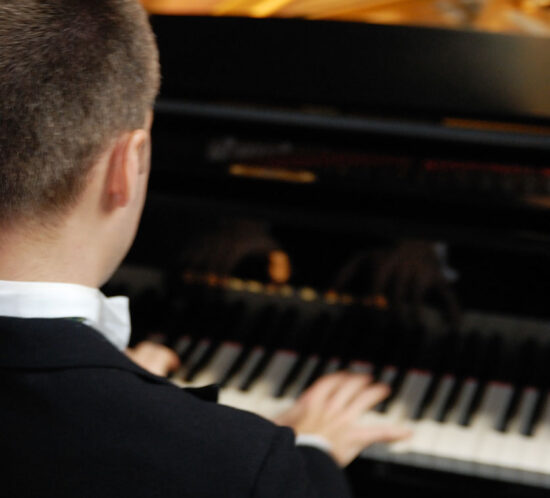 Robin Hutt playing piano over shoulder